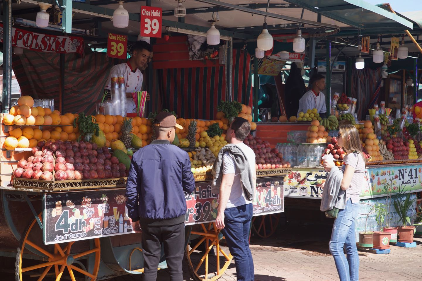 People buying juices on a food stall on Jemaa el-Fnaa durning daytime.